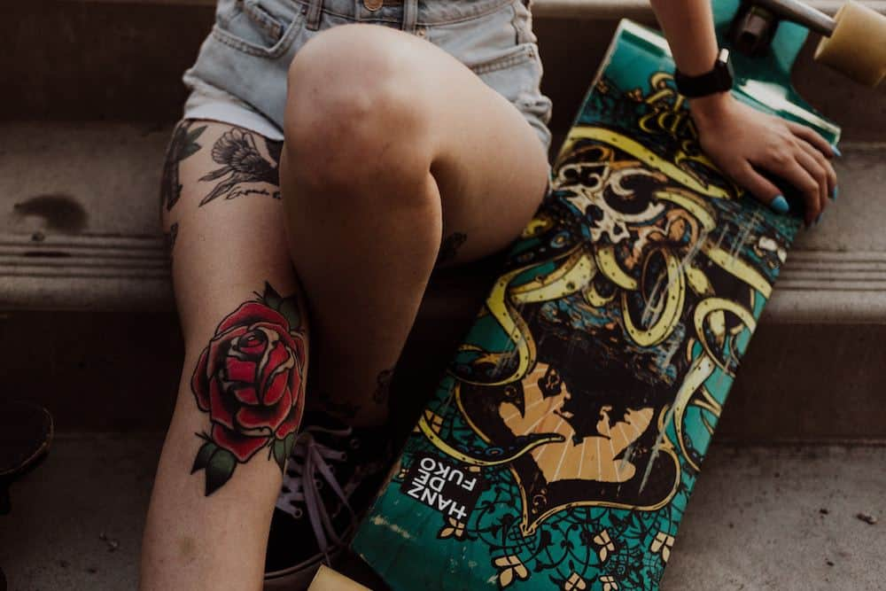 Girl with tattoos siting with longboard